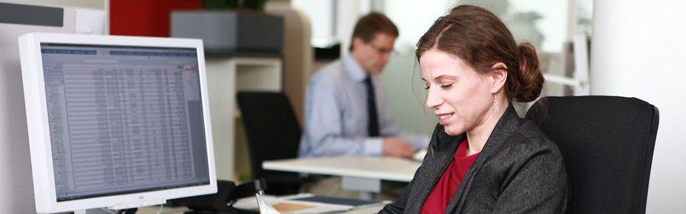 Mitarbeiterin mit Tablet vor Computerarbeitsplatz im Großraumbüro